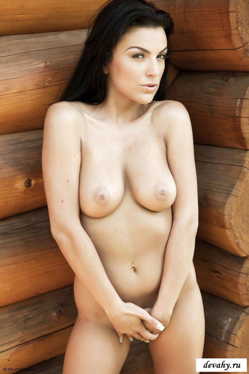 Раздетая модель с темными волосами в дачном доме