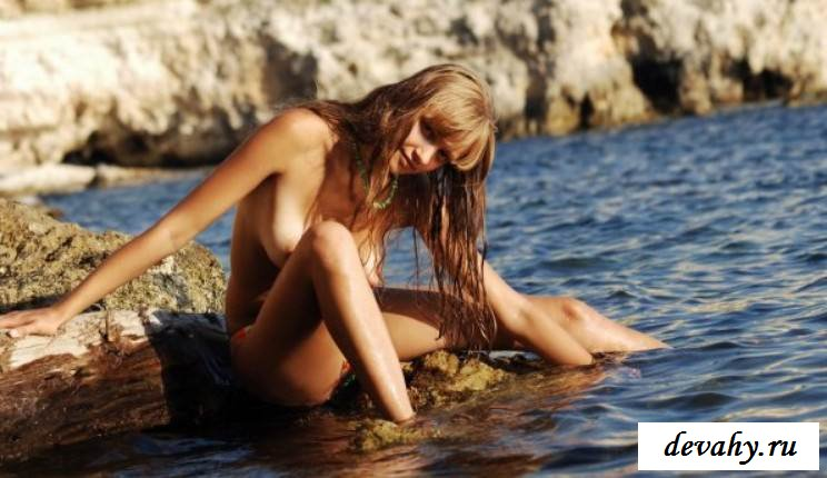 Чика лежит на солнышке на камнях с голым бюстом (эротика)