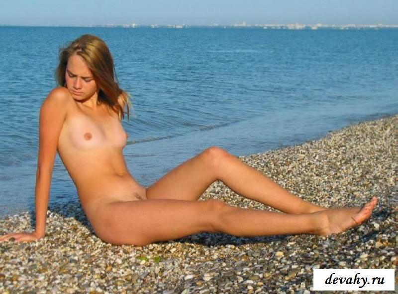 Голая девица принимает позы на пустынном берегу (15 фото эротики)