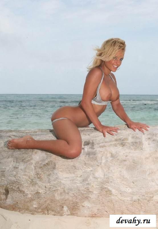Светловолосая девушка с большими грудями обнажилась на песке (15 эротических снимков)