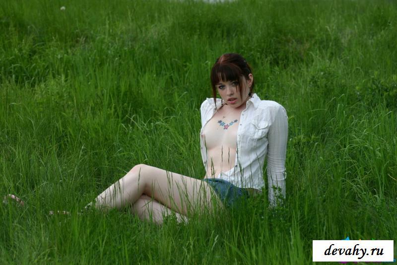 На фото голой молоденькой девушки на траве показала грудь